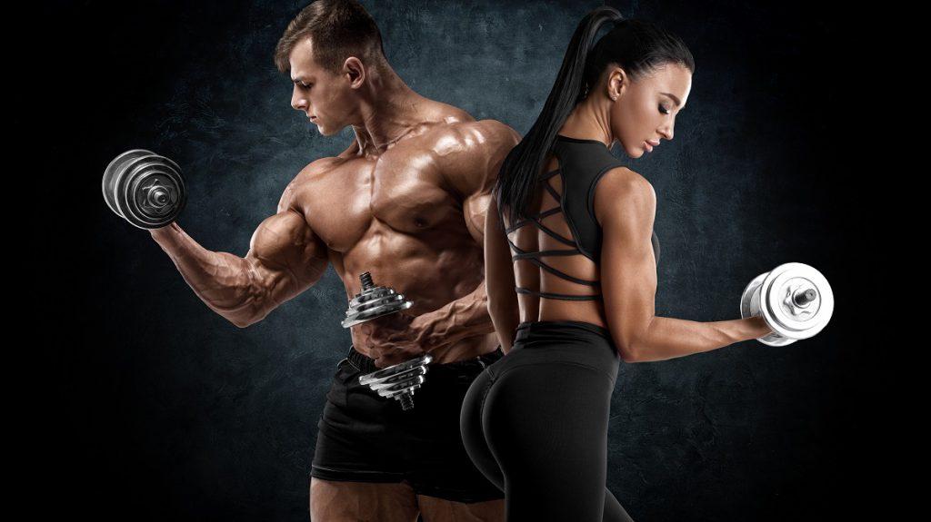 Sportowy trening para z hantlami. Muskularny mężczyzna i kobieta pokazując mięśnie